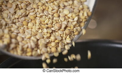 Cooking yellow split pea. Pouring split peas into the pot in...