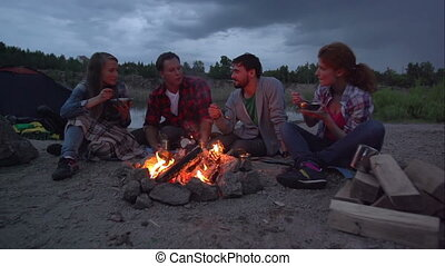 Cookout by Fire - Pan of four friends having meal at...