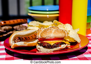Cookout with cheeseburger, hot dog and potato chips. Mustard and ketchup bottles, bowls, hamburger patties, and hot dog wieners in background.