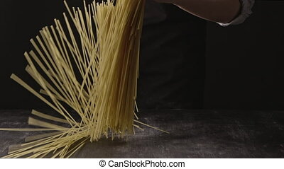 Cook's hand throws raw uncooked italian pasta on a wooden...
