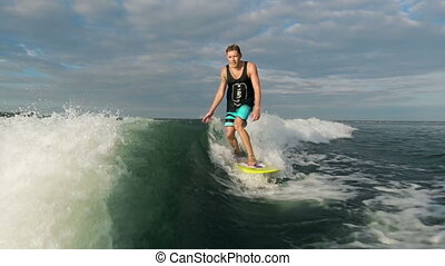 Cool Adventure - Tracking shot of wake surfer catching waves...
