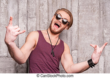 Cool and funky. Handsome young man in sunglasses making a face and gesturing