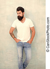 Cool and sexy. male fashion trends. Simple and casual summer. Brutal macho gray background. Male temper brutality. bearded man radiate masculinity. physical attractiveness. handsome hipster jeans