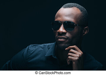 Cool and trendy. Portrait of handsome young African man in sunglasses holding hand on chin and looking away while being in front of black background