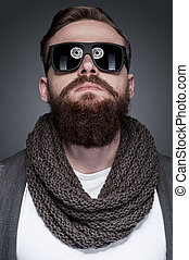 Cool and trendy. Portrait of handsome young bearded man in sunglasses standing against grey background