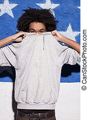 Cool and young. Young African man hiding his face in his...