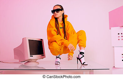 Cool asian female office worker in sunglasses on table with obsolete computer. Colored light