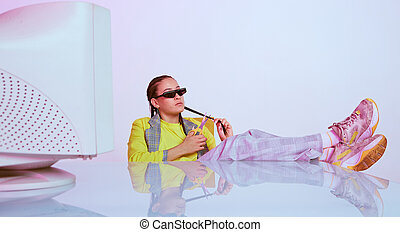 Cool asian female office worker in sunglasses sitting with obsolete computer with feet on table