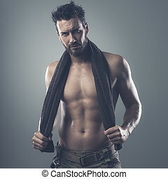 Cool athletic man posing with towel - Confident muscular man...