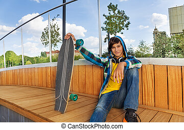Cool boy with skateboard sits in park