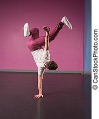 Cool break dancer doing handstand on one hand in the dance...