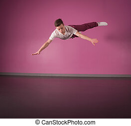 Cool break dancer mid air in the dance studio