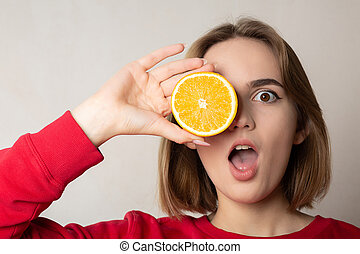 Cool brunette girl posing with a half orange, covering one eye, against white wall. Space for text