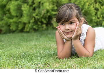 Cool brunette little girl lying on the grass