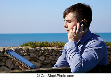 Cool businessman working with tablet and phone outdoors