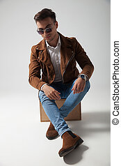cool casual man resting on a wooden box