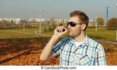 cool caucasian guy in black glasses and shirt smokes vape,...