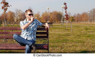 Cool caucasian man in black glasses sits on a bench and...