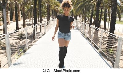 Cool ethnic woman walking on sunny street - Trendy young...