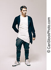 Cool fashion male model posing. Street youth fashion. Sneakers, t-shirt, cardigan, pants, trousers. Studio. Indoor.