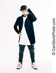 Cool fashion male model posing. Street youth fashion. Sneakers, t-shirt, cardigan, pants, trousers. Baseball cap. Studio. Indoor.