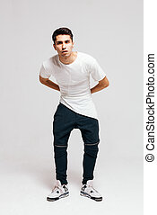 Cool fashion male model posing. Street youth fashion. Sneakers, t-shirt, pants, trousers. Studio. Indoor.