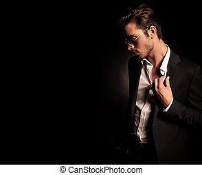 cool fashion man in suit and sunglasses pulling his collar -...