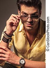 cool fashion model taking off his sunglasses