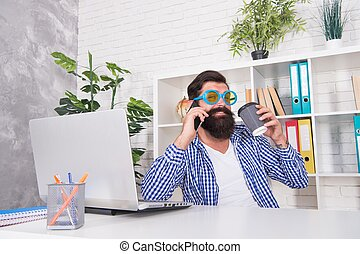 Cool freelancer in fancy glasses talk on mobile phone drinking coffee in modern office, morning