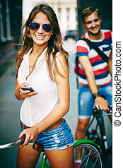 Cool girl - Portrait of happy young couple on bicycles,...