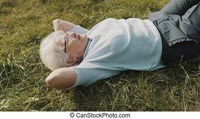 Cool grandma lying on the grass with hands under her head. Resting in nature
