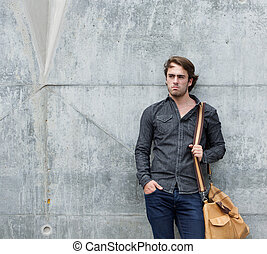 Cool guy posing with bag outdoors