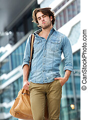Cool guy posing with leather bag outside