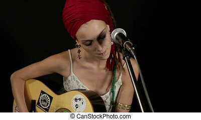 cool gypsy style woman plays guitar and sings