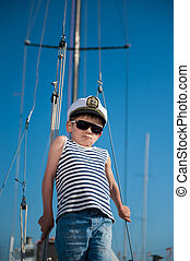 cool handsome little kid captain aboard luxury yacht on blue...