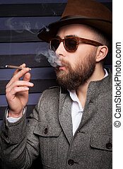 Cool handsome smoking. Side view of handsome young man in sunglasses smoking a cigarette