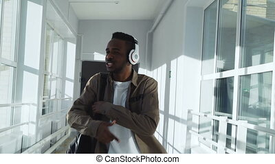 Cool happy african american guy dancing listening to music...