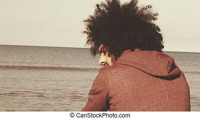 Sad lonely man sitting on the beach thinking closeup