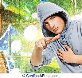 Cool looking man in a hood over abstract graffiti background