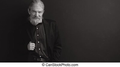 Cool man in formal wear, tux standing in a studio on black background, looking to the camera, shares, stock, money. Black and white. Prores 422.