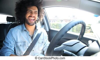 Handsome man singing and dancing like crazy while driving car