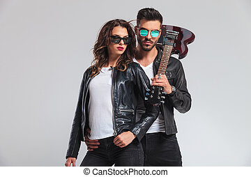 cool rock and roll couple posing on grey studio background