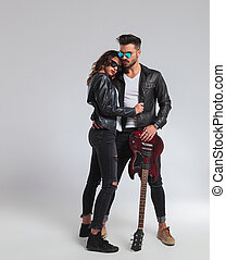cool rock and roll couple standing embraced, full body...