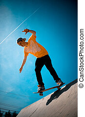 Cool Skateboarder - A young man skateboarding down a ramp at...