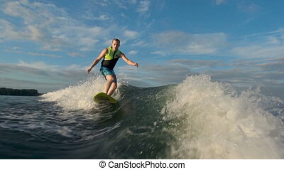 Cool Surfer - Man in life vest approaching camera riding...