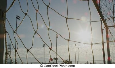 Close-up tilt up shot of a soccer net on a field with nobody around