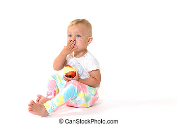 Cool toddler girl is holding a red apple