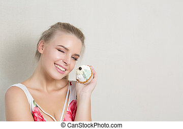 Cool winking blonde woman with perfect makeup holding sweet cream dessert. Space for text