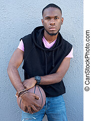 Cool young african american guy holding basketball