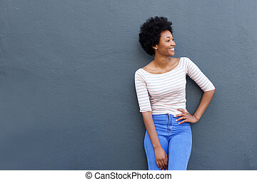 Cool young african woman smiling against gray background